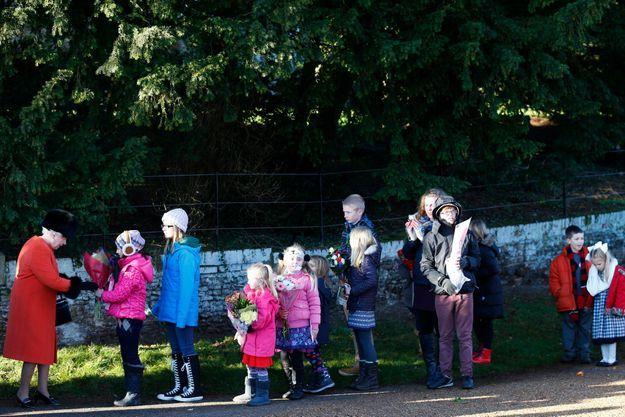 La reine Elizabeth acceptant les fleurs des enfants, lors du dernier noël à Sandringham.