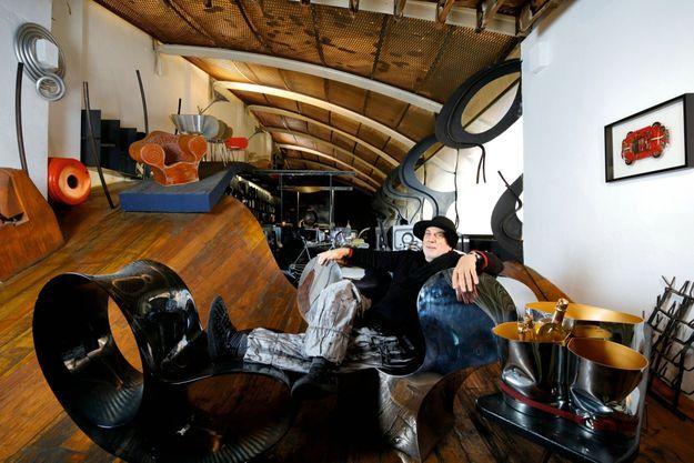 Ron Arad dans son studio londonien, avec la vasque en étain « Trio » livrée avec des cuvées Dom Ruinart d'exception et une malle écrin de chêne. Une édition limitée à 15 000 euros. Fauteuils Oh Void et Big Easy