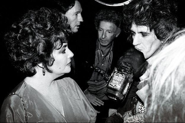 Liz Taylor et Keith Richards au Roxy Roller Disco, New York, en 1980. Le guitariste des Rolling Stones boit du Jack Daniel's à la bouteille en pleine discussion avec l'actrice. Pour l'impressionner ?