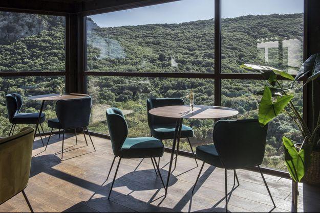 La salle du restaurant offre une vue spectaculaire sur les collines et le lac des Olivettes.