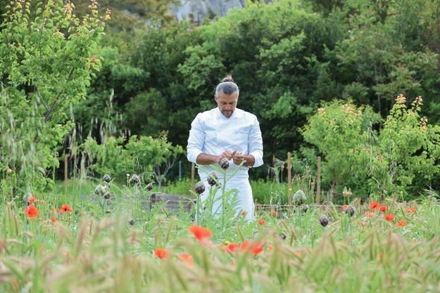 Glenn Viel en train d'expertiser un légume dans son jardin potager.