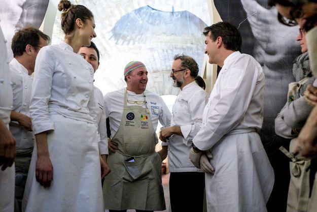 Le soir de l'ouverture, Yannick Alléno (à dr.) a concocté le premier menu du Refettorio parisien à l'invitation de Massimo Bottura. Avec eux, les bénévoles et le chef italien (au bonnet) Pasquale Torrente.