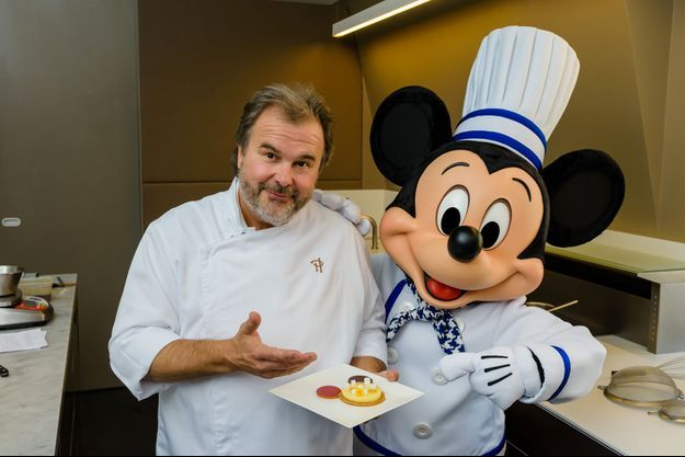 Pierre Hermé pose à côté de Mickey pour présenter son gâteau d'anniversaire.