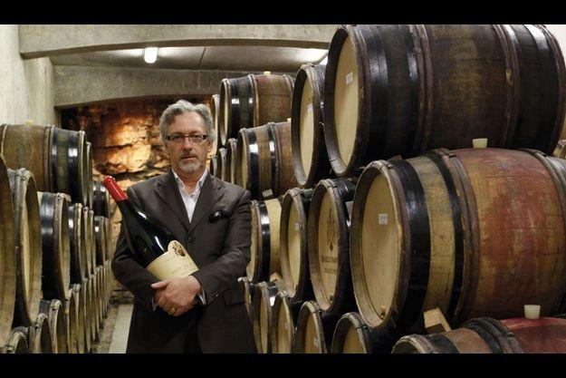 Laurent Ponsot dans ses chais, avec une authentique bouteille de son vignoble.