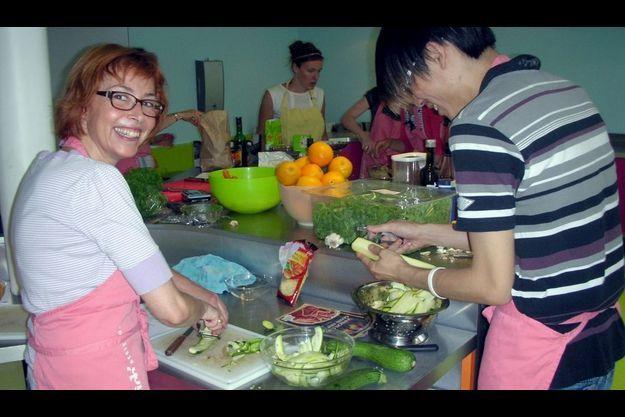 Brigitte et Alain préparent un sandwich à base de courgette et de pesto de roquette. En arrière-plan, la chef Chloé Baeyaert.