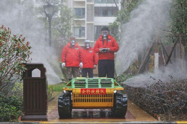 A Wuhan, berceau de l'épidémie, un volontaire dirige un robot qui pulvérise un désinfectant à travers la ville.