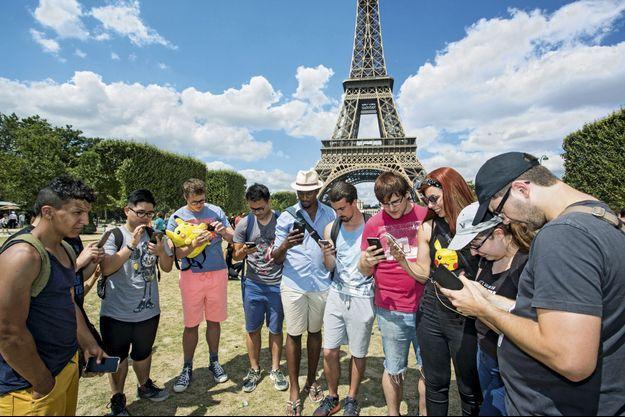 Au Champ-de-Mars, le 24 juillet. Des groupes se forment au hasard de la traque des Pokémon.