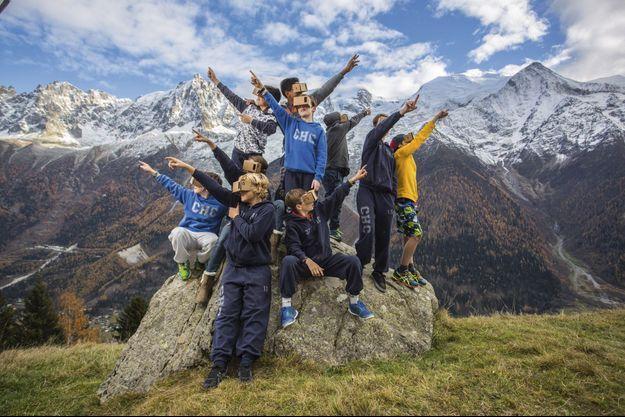 Equipés du Cardboard de Google, dans lequel ils ont inséré un Smartphone, de jeunes membres du Club de hockey sur glace de Chamonix (CHC) dans le parc de Merlet, devant le massif du Mont-Blanc.