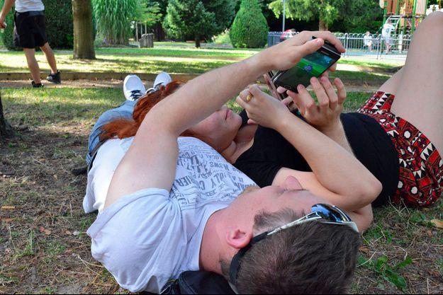 Deux Français jouent à Pokémon Go, allongés dans un parc