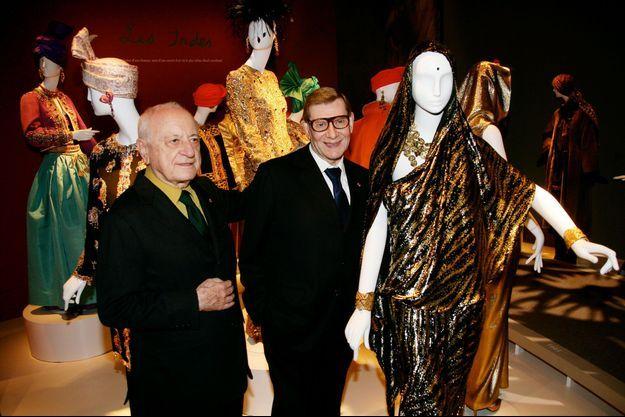 """Pierre Bergé et Yves Saint Laurent au milieu des modèles de l'exposition """"Voyages extraordinaires"""", en octobre 2006."""