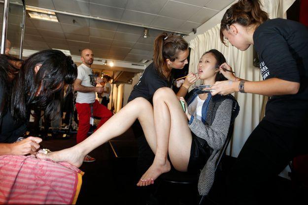 Un mannequin se fait maquiller de la tête aux pieds avant le défilé Christine Phung.