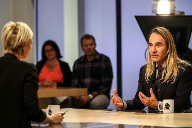 """John Galliano sur le plateau du """"Supplément"""" sur Canal+, avec Maïtena Biraben, le 14 septembre 2014."""