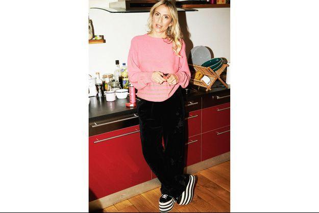 Lola Rykiel dans sa cuisine, à Paris : l'art du chic'n'cool, glissée dans un pull en maille Sonia Rykiel vintage, un jogging Pompom en velours, l'ensemble twisté d'une paire de basket compensée griffée Gucci.