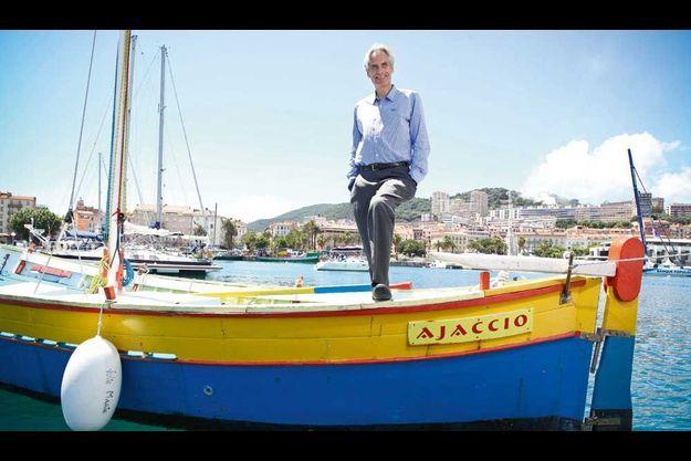 Charles Napoléon sur un simple bateau de pêcheur... Derrière lui, le vieil Ajaccio, où l'on peut visiter la maison natale de Bonaparte.
