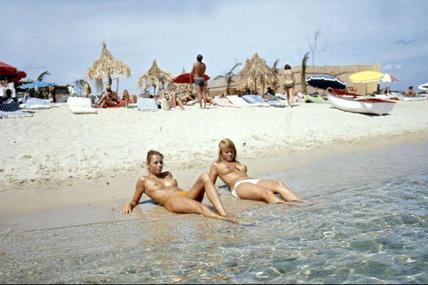 Saint-Tropez - août 1970 - Sur la plage de la Voile Rouge à Pampelonne, allongées sur le rivage, deux femmes aux seins nus baignant leurs pieds dans l'eau