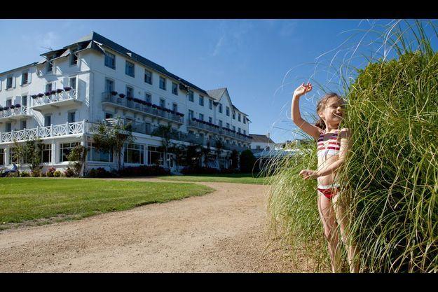 Marion, qui passe ses vacances sur cette côte, batifole dans les herbes hautes du parc de l'hôtel de Locquirec. Sa façade est inchangée depuis sa construction dans les années 20.