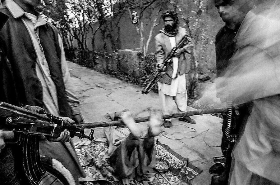 A Taliban is being punished by Mojahedin after being captured by them in Herat, Afghanistan 2001.