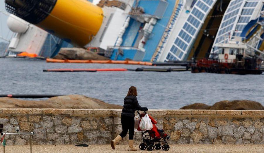Une femme promène son enfant à proximité du navire échoué Costa Concordia sur l'île du Giglio. Le mauvais temps a retardé les opérations de pompage des cuves du bateau de croisière, qui contiennent 2300 tonnes de carburant.