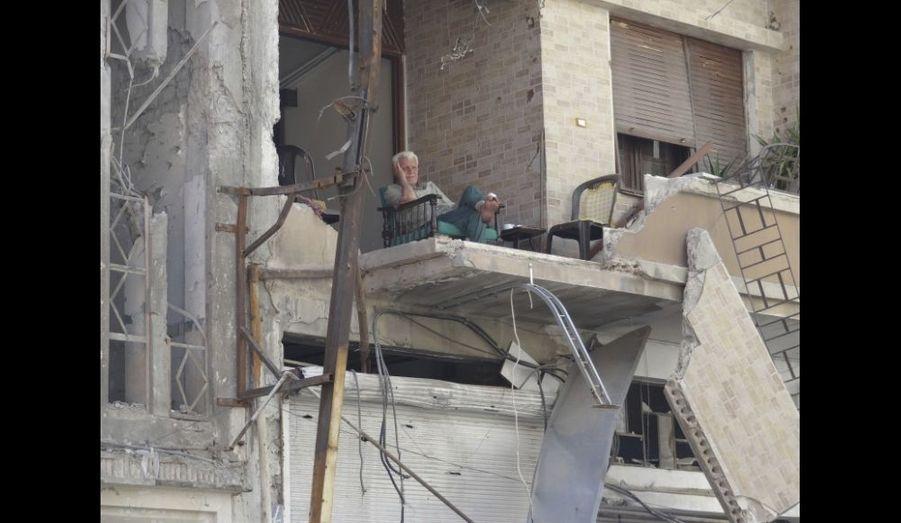 Un homme attend, assis dans les ruines ouvertes de sa maison, à Homs, en Syrie.