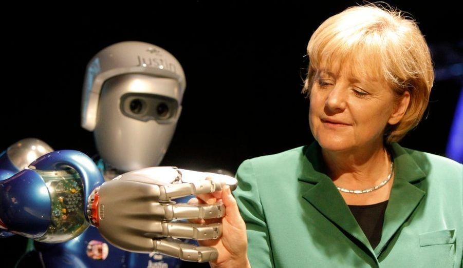 La chancelière allemande, Angela Merkel, serre la main du robot « Justin » à l'ILA Berlin Air Show 2010, salon aéronautique qui se déroule à l'aéroport de Schönefeld jusqu'au 13 juin.
