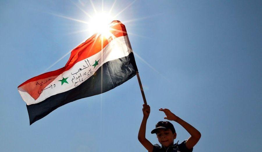 """Un enfant tient un drapeau syrien lors d'une manifestation près de Mafraq, en Jordanie. """"Nous demandons l'exécution des tueurs et la liberté"""", est-il écrit en arabe."""