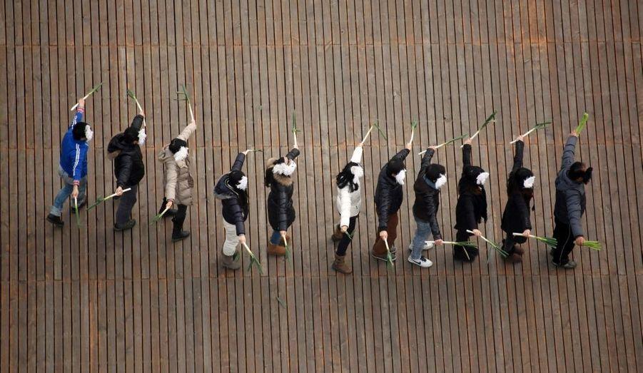 Des habitants de Shanghai pratique une danse avec des échalotes, à l'occasion du nouvel an chinois qui sera fêté le 23 janvier prochain.