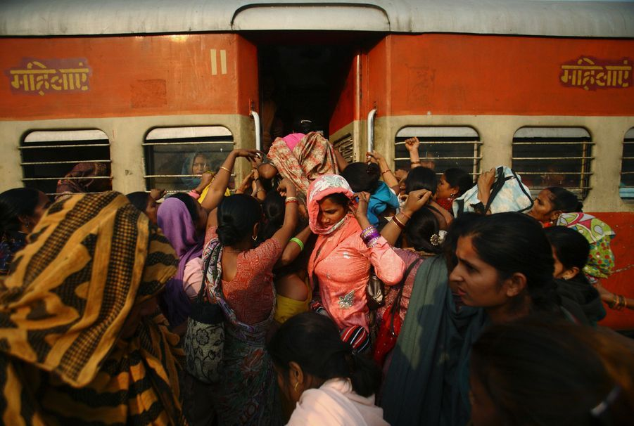 """Des Indiennes tentent d'entrer dans le compartiment bondé réservé aux dames à la station de chemin de fer Noli dans l'Uttar Pradesh. Ces wagons ont été créés dans un effort d'améliorer la sécurité des femmes en Inde. La question féminine est au coeur du débat dans le pays depuis le viol d'une étudiante de 23 ans à Delhi le 16 décembre. Jyoti Singh Pandey, """"la fille de l'Inde"""", est décédée dans un hôpital de Singapour le 28 décembre des suites de ses blessures."""