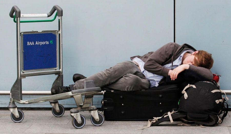 A l'aéroport d'Heathrow, un voyageur exténué s'improvise un lit de fortune. Une vingtaine d'aéroports ont été fermés ce matin en Grande-Bretagne, en Irlande et aux Pays-Bas, en raison des cendres en suspension du volcan islandais Eyjafjöll.