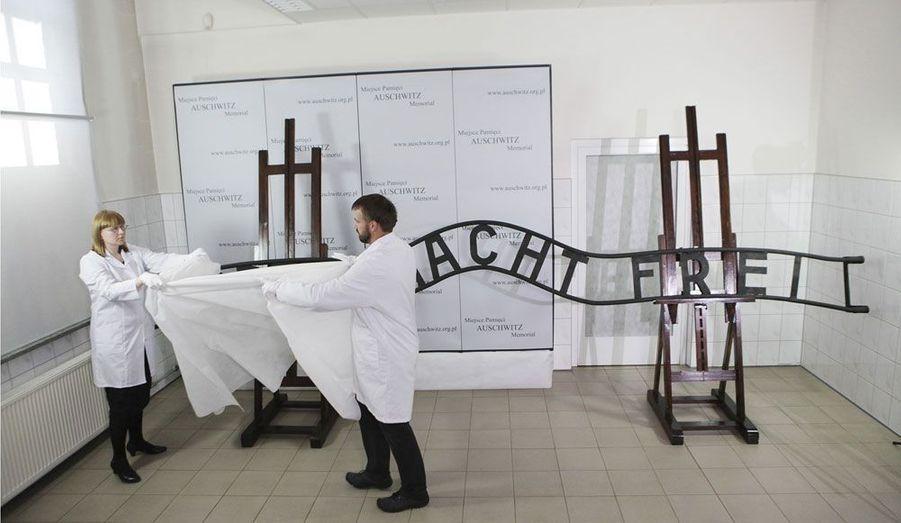 """Ce panneau portant l'inscription """"Arbeit macht frei"""" (""""le travail rend libre"""") a été restauré en Pologne. Des voleurs l'avaient dérobé à l'entrée du camp d'Auschwitz, le découpant en trois parties pour pouvoir l'emporter. L'inscription est l'un des symboles de l'Holocauste et du système concentrationnaire nazi."""