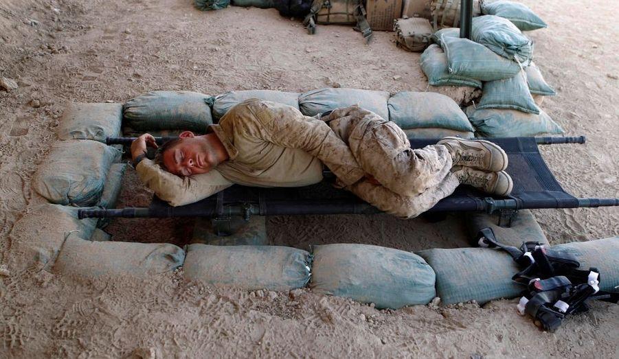 Un Marine américain du 1er Bataillon dort sur une civière à l'ombre, dans un poste avancé Kunjak, dans la province méridionale d'Helmand en Afghanistan.
