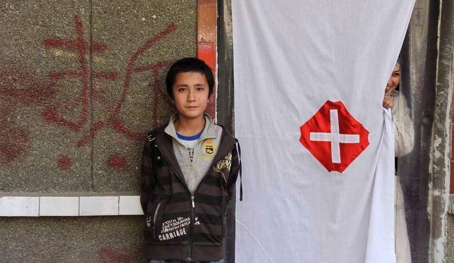 Un garçon et une fille ouïghours à l'entrée d'une clinique de lutte contre la pauvreté à Aksou, dans la région autonome du Xinjiang en Chine.