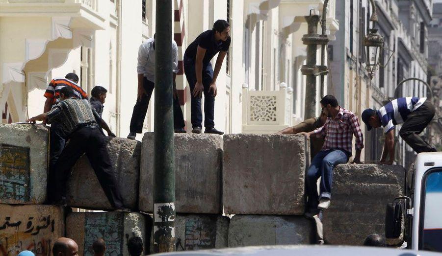 Des manifestants sautent les barrières installées par les militaires et censées bloquer un passage menant à la Place Tahrir en Egypte.