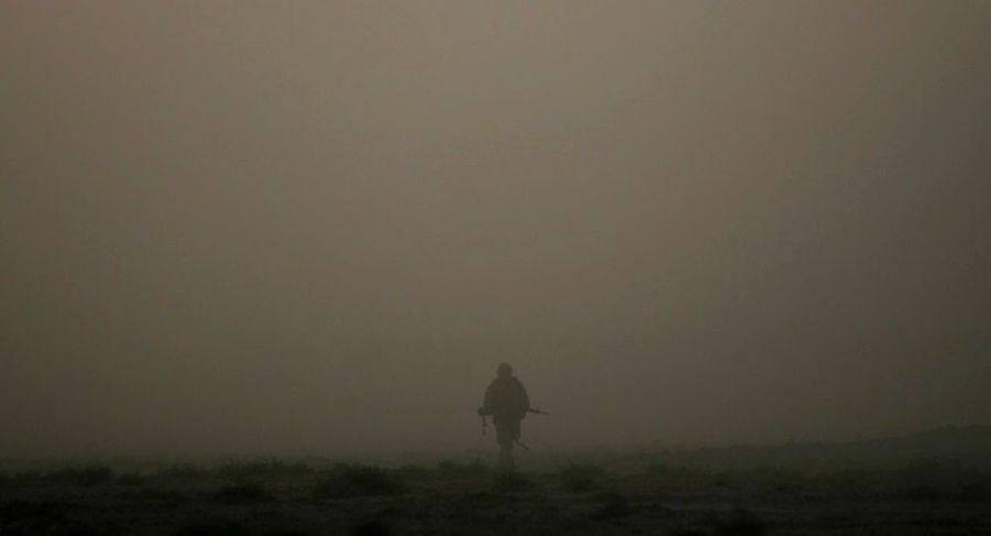 Un soldat canadien isolé au milieu d'un nuage de poussière lors d'une opération dans la province de Kandahar en Afghanistan
