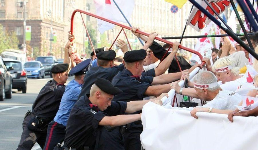 Des officiers du ministère de l'Intérieur bloquent des partisans de l'ancien Premier ministre ukrainien, Ioulia Timochenko, vendredi, à Kiev. L'ex-chef du gouvernement a comparu devant le tribunal lors d'une audience préliminaire pour «abus de pouvoir». Elle est accusée d'avoir signé, en 2009, un contrat d'importation de gaz avec la Russie à des tarifs jugés trop élevés. Ioulia Timochenko, qui rejette ces accusations, se dit victime d'un complot politique fomenté par son rival, le président Viktor Ianoukovitch.