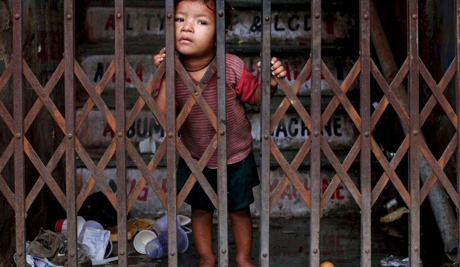 Un enfant derrière les grilles d'une boutique, dans les rues du «vieux» Dehli, avant l'ouverture du marché.