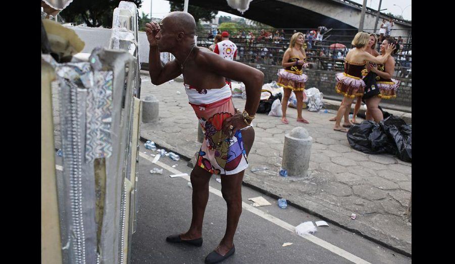 Un homme se maquille dans la rue juste avant de défiler sur l'avenue Sambadrone, longue de 700 mètres, à l'occasion de l'événement de l'année: le Carnaval de Rio.