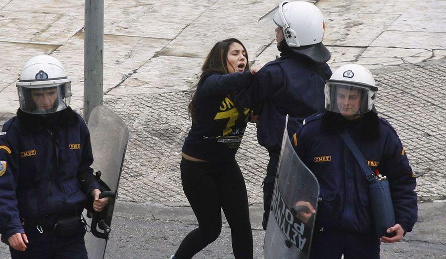 Une lycéenne est brièvement arrêtée par les forces de l'ordre grecques après qu'une centaine de jeunes aient bloqués la circulation devant le Parlement à Athènes.