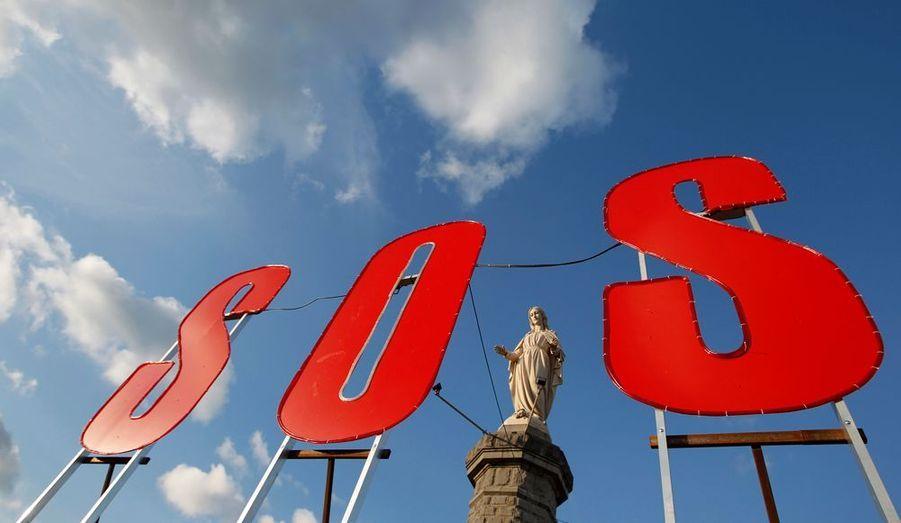 Suite à la récente fermeture de hauts-fourneaux à Liège et Madrid, l'usine de Florange en Moselle est à l'arrêt, et les syndicats occupent les bureaux depuis hier. ArcelorMittal assure que l'usine de Lorraine ne connaîtra qu'une mise en veille temporaire. Comme un appel au secours, un signe S.O.S a été disposé devant une statue de la Vierge Marie.