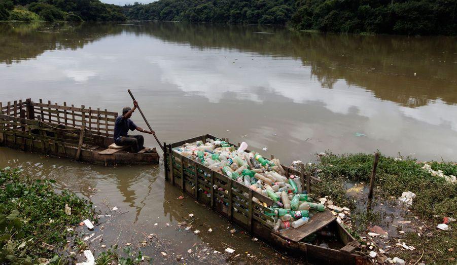 Roberto da Silva pousse un de ses bateaux rempli de bouteilles en plastique qu'il a pêché dans les eaux polluées de la rivière Tiene à Santana do Parnaiba, à 32 km de Sao Paulo au Brésil. Cette rivière est l'une des plus polluées du pays.