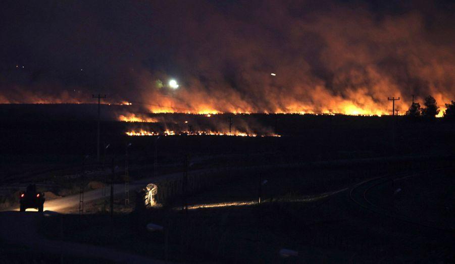 Vue nocturne sur la frontière entre la Turquie et la Syrie. Au loin, la ville de Ras al-Ain est en flammes, témoignage des combats menés dans cette localité frontalière.