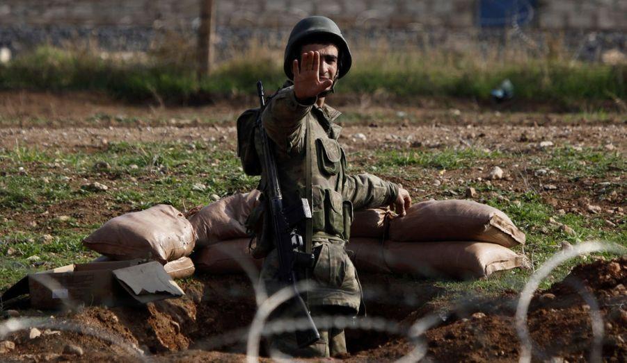 Un soldat turc demande aux médias de reculer, à la frontière avec la Syrie.