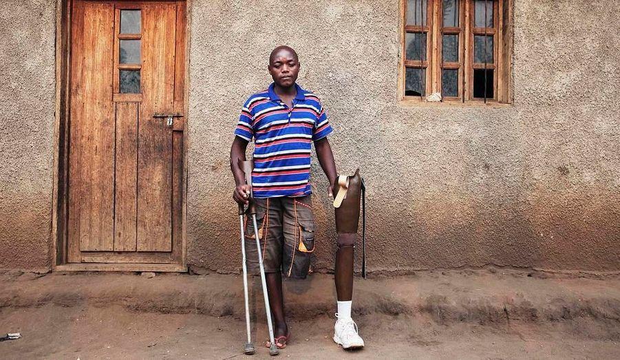 Jean Claude Benda, amputé de guerre, pose devant sa maison à côté de sa prothèse. Il s'est fait tirer dessus lors d'un massacre en République Démocratique du Congo, le 4 novembre 2008, qui avait fait 150 morts. Il n'est plus capable de travailler en tant que fermier, il doit donc compter sur sa femme enceinte et ses cinq enfants pour subvenir aux besoins de la famille.