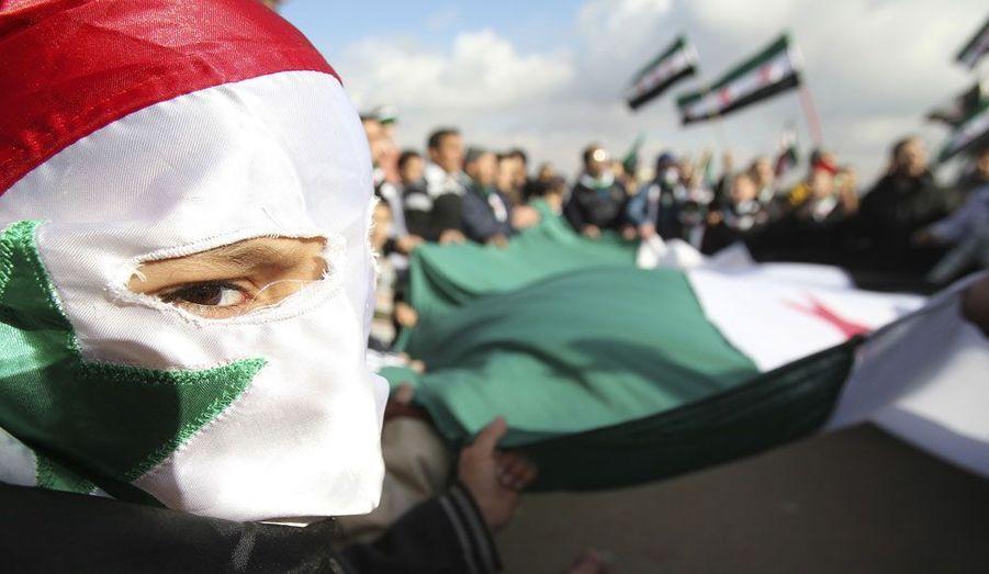 Le visage camouflé par un drapeau découpé, un Syrien manifeste contre le régime de Bashar Al-Assad devant l'ambassade d'Amman.
