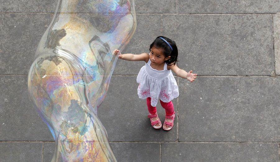 Bea Duva, une petite anglaise de trois ans, joue avec des bulles de savon à Londres, alors que les températures ont atteint les 25 degrés.