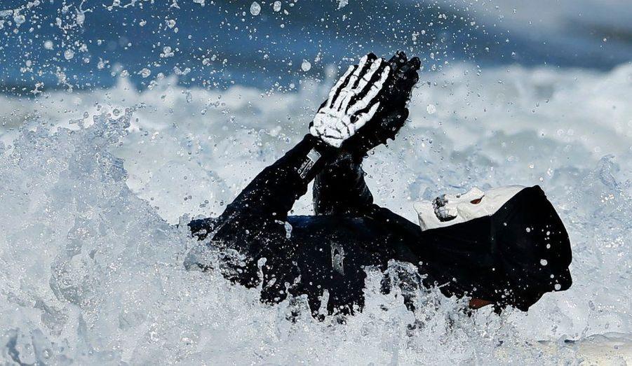 Quelques jours avant Halloween, un participant du ZJ Boarding House Halloween surf contest prend un bain de mer à Santa Monica, en Californie.