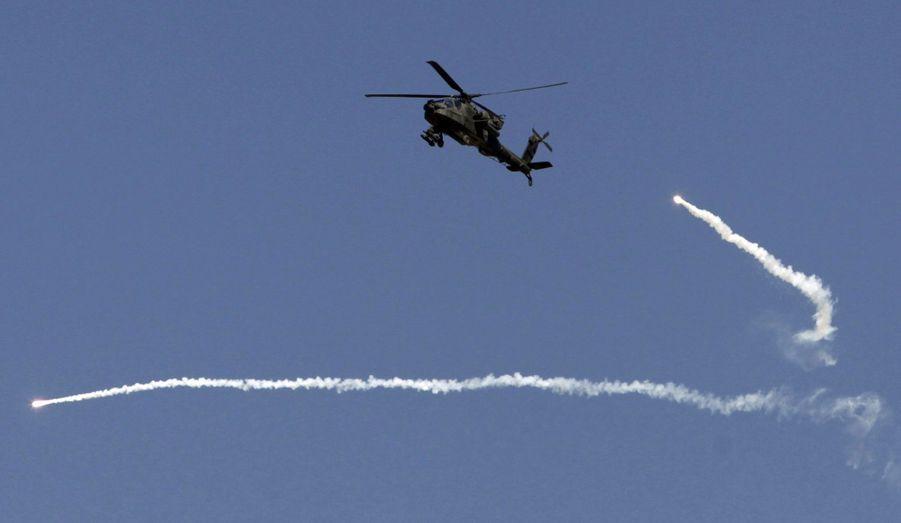 Un hélicoptère de l'armée américaine Apache tire des leurres en passant au dessus d'un poste de combat en Afghanistan, dans la province de Kandahar.