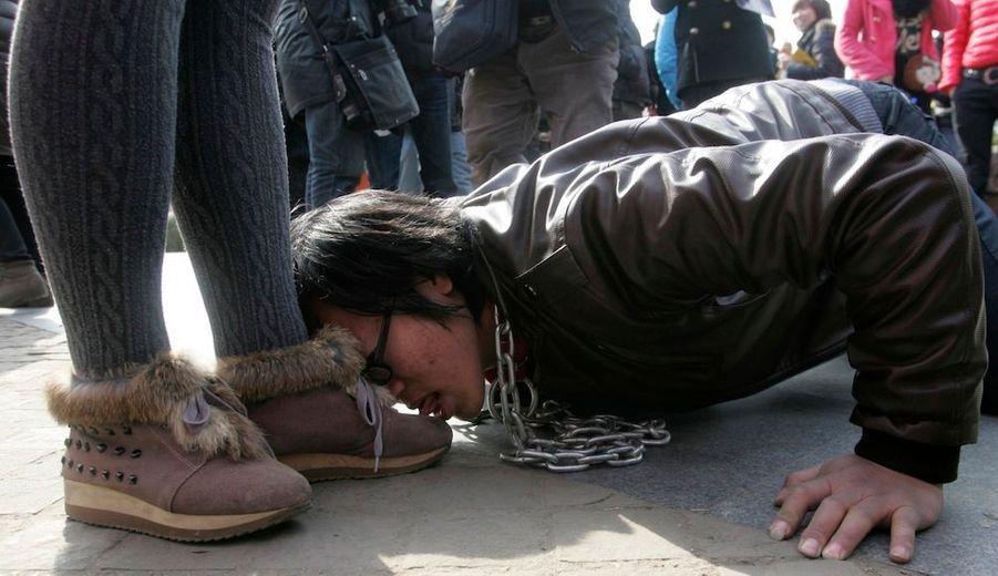 Un hommeavec une chaîneautour du coulècheleschaussuresd'une femmelors d'une performanceà Wuhan,dans laprovince du Hubei en Chine,appelant à l'égalitéentre hommeset femmes.