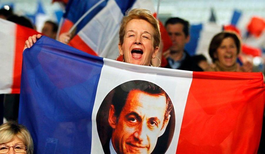 Une militante, brandissant un drapeau avec le portrait de Nicolas Sarkozy lors de son grand meeting dimanche à Villepinte, en Seine-Saint-Denis.