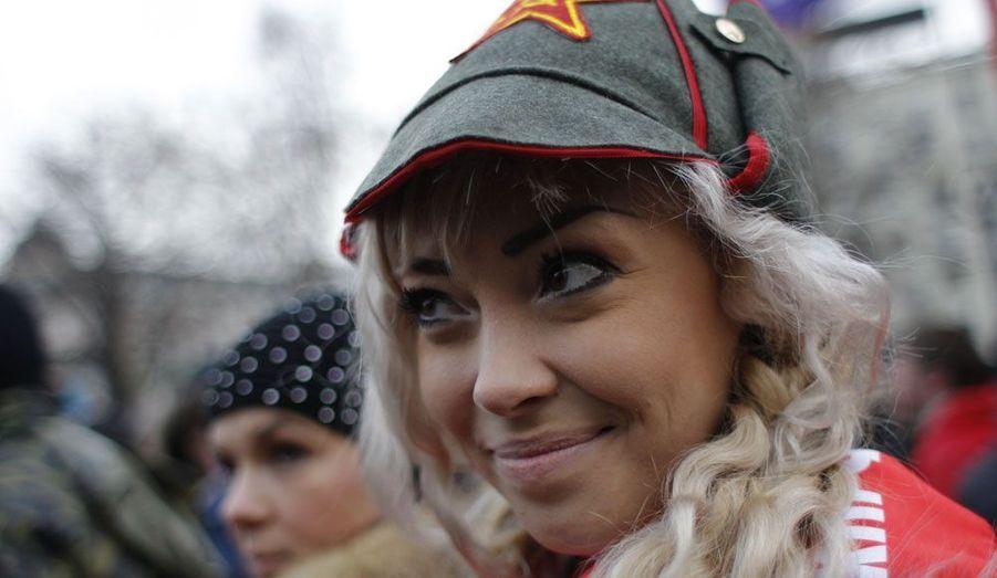 Une jeune femme manifeste en Russie. Accompagnée de centaines d'autres opposants, elle prône des élections justes, quelques heures après la victoire de Vladimir Poutine à la présidentielle.
