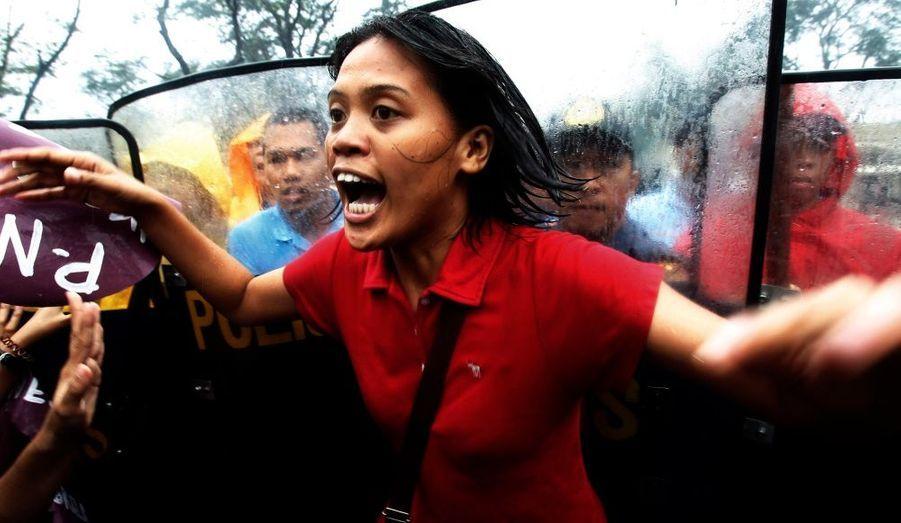 Une jeune Philippine manifeste, dos aux policiers anti-émeutes, dans les rues de Manille. Elle proteste pour le maintien de la journée de la femme, demain, et contre les politiques du gouvernement actuel.